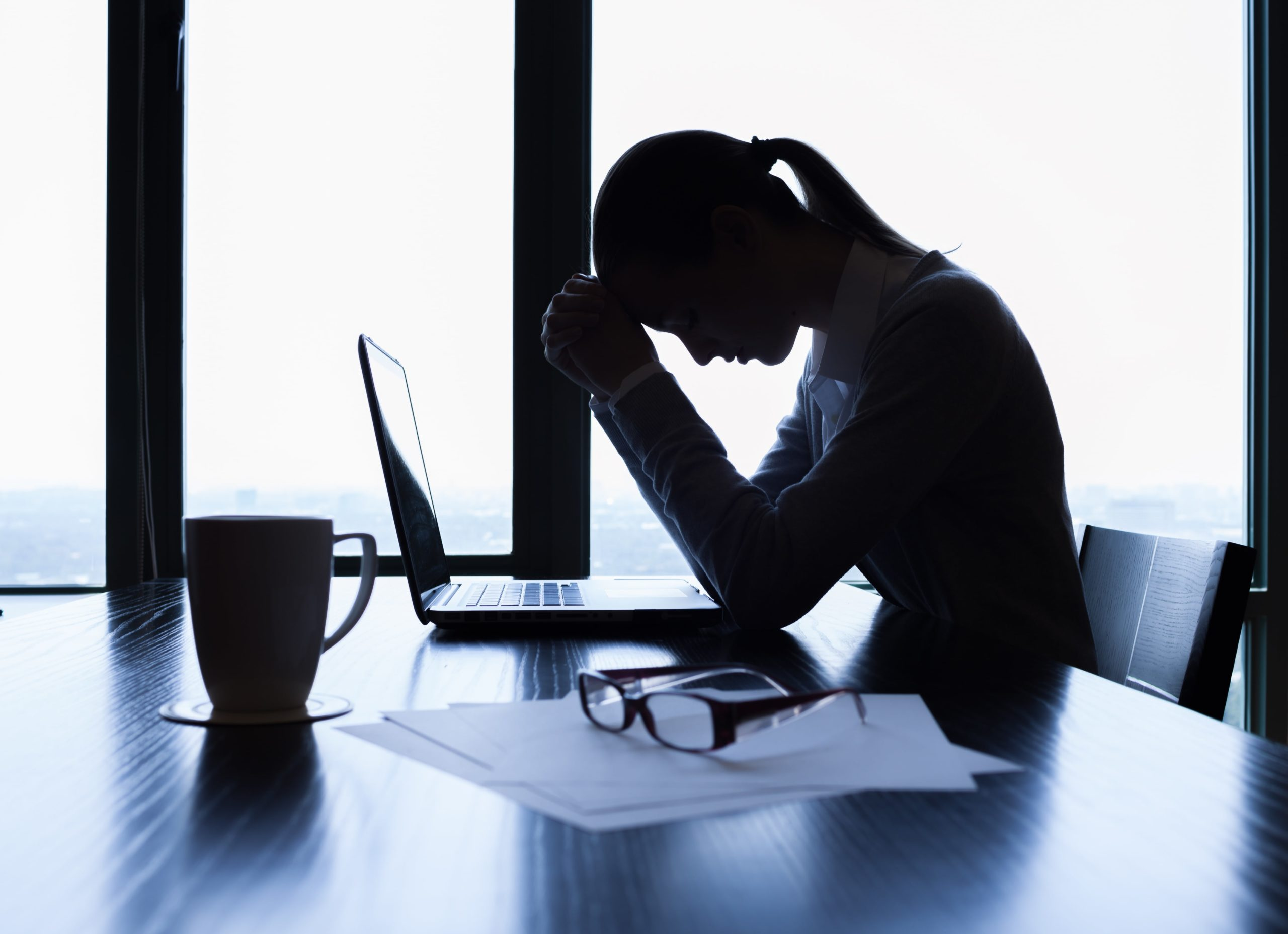 Woman on a computer experiencing headaches and fatigue, potential side effects of carbidopa levodopa